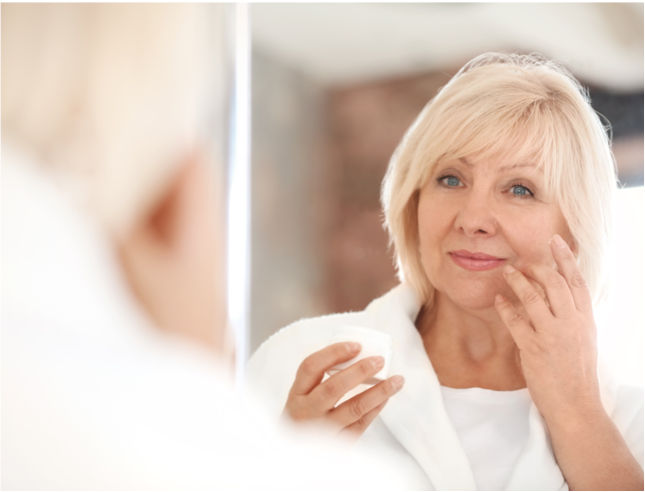 An older woman looking in the mirror putting on face cream.